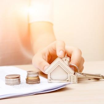 Frauenhand mit geld und grundstellungstaste. unterzeichneter vertrag und schlüssel des eigentums mit dokumenten. konzept für das immobiliengeschäft.