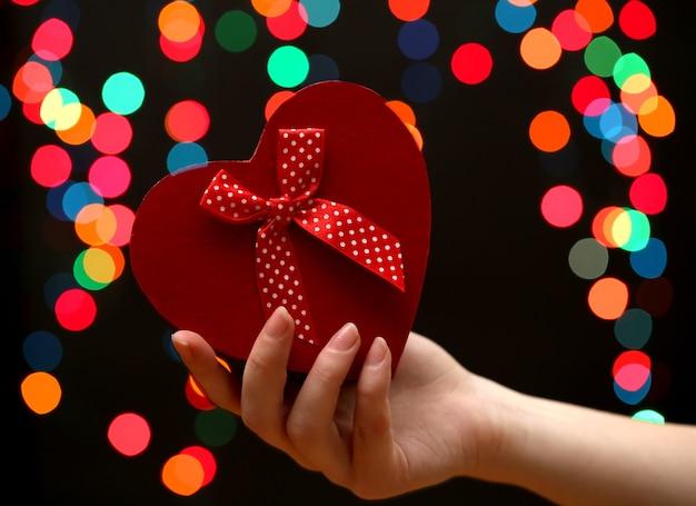 Frauenhand mit geschenkbox, auf girlandenhintergrund