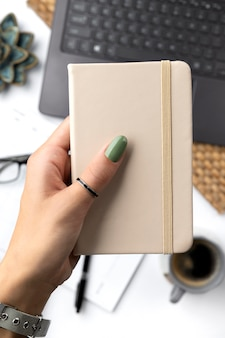 Frauenhand mit grünem frühlingssommermaniküre, der notizblock hält