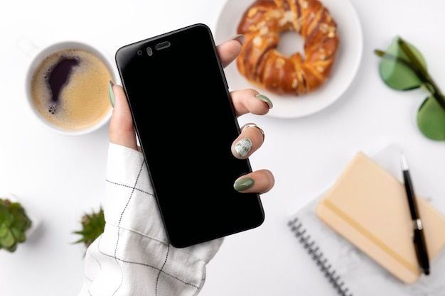 Frauenhand mit grüner frühlingssommermaniküre, die smartphone hält