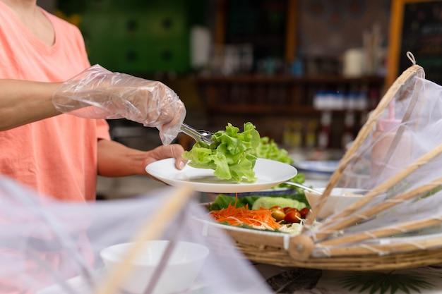 Frauenhand mit handschuh, der salatgemüse für salat am buffet nimmt.