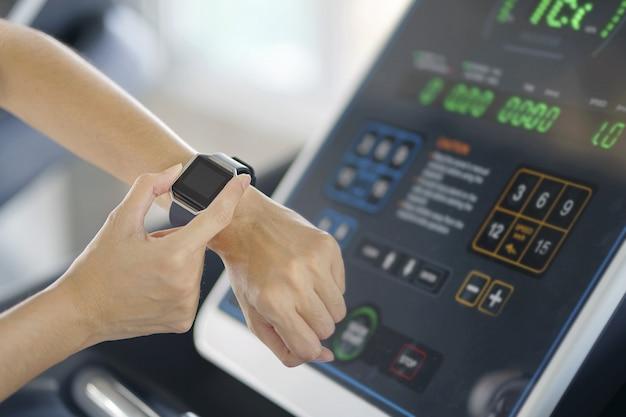 Frauenhand mit intelligenter uhr auf handgelenk, tragbares eignungsgerät, sportlicher läufer, der den übungslauf innen tut und gewichtsverlust mit der maschine aerob nimmt. gesunder sport cardio stark.