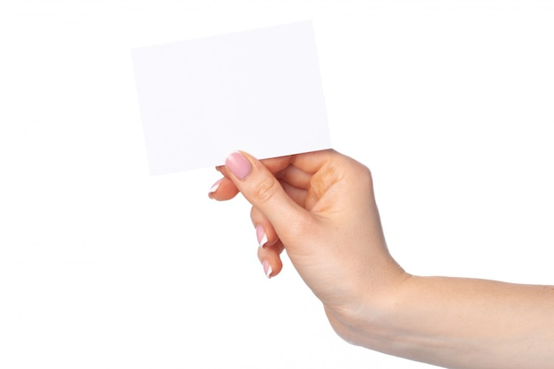 Frauenhand mit leerer weißer visitenkarte lokalisiert auf weiß