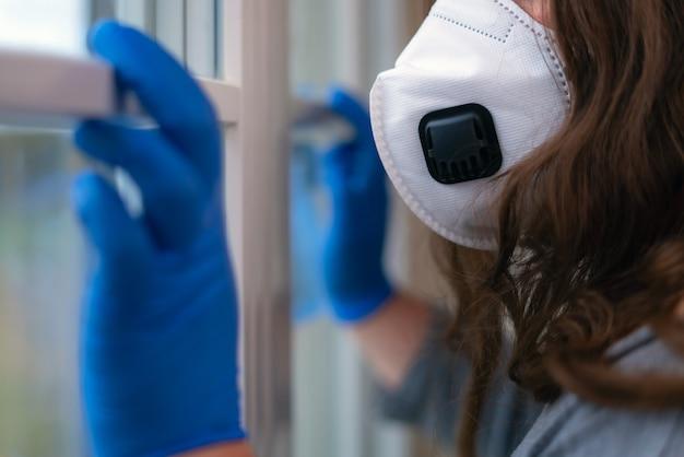 Frauenhand mit medizinischen handschuhen neben dem fenster innen.