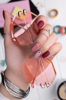 Frauenhand mit minimalem rosa frühlingssommermaniküreentwurf, der sonnenbrille hält