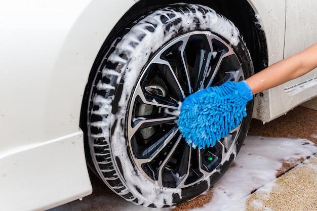 Frauenhand mit modernem auto des blauen mikrofasergewebes waschendem rad oder reinigungsautomobil.