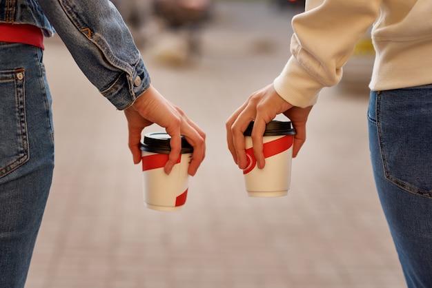 Frauenhand mit papiertasse kaffee nehmen in einer stadtstraße weg
