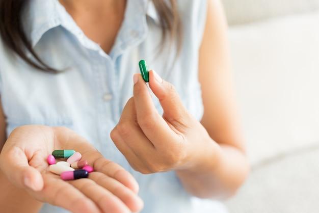 Frauenhand mit pillenmedizintabletten und -kapsel in ihren händen.