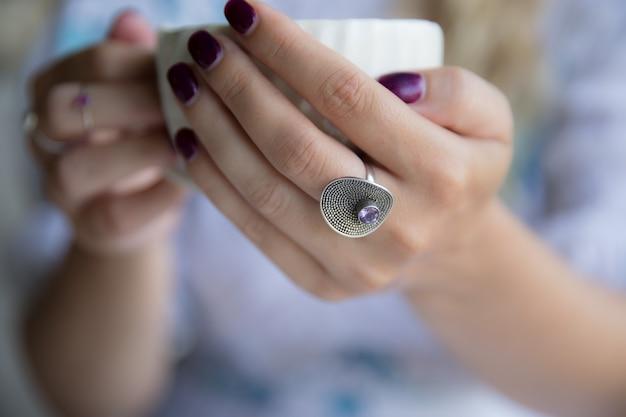 Frauenhand mit ring, der tasse cappuccino hält