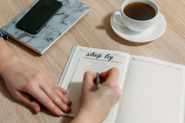 Frauenhand mit schlafprotokoll oder tagebuch auf tisch