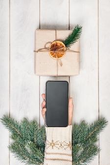 Frauenhand mit smartphone, neujahrsgeschenk im öko-stil, tannenzweige