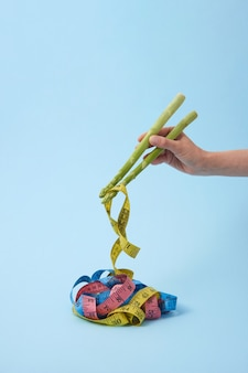Frauenhand mit spargelstangen nimmt maßbänder als bunte nudel gegen pastellblauen hintergrund, kopierraum. farbige maßbänder als japanisches oder chinesisches essen.