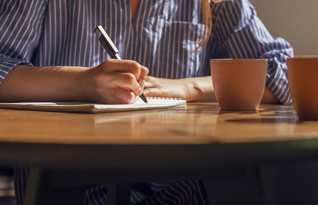 Frauenhand mit stift, der notizen macht, pläne im planer auf holztisch mit teetassen im kaffeehaus schreiben?
