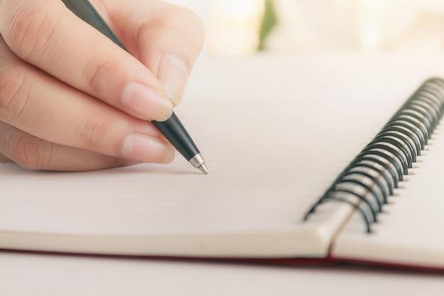 Frauenhand mit stiftschreiben auf notizbuch