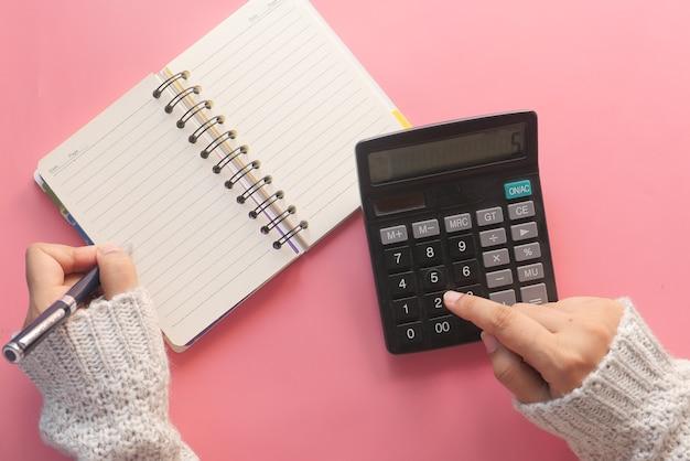 Frauenhand mit taschenrechner auf rosa hintergrund