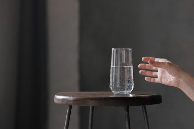Frauenhand nimmt ein glas wasser, trinkflüssigkeit für die körpergesundheit, kohlensäurehaltig oder still, wassertrinkprogramm zu hause, dehydration oder durst