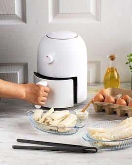 Frauenhand öffnen airfryer-behälter. eine weiße fritteuse oder eine ölfreie fritteuse, eine zange, eine klare backform und ein eiertablett stehen auf dem holztisch in der küche mit einer kleinen pflanze im topf (luftfritteuse)