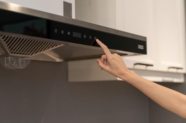Frauenhand öffnet küchenhaube zum kochen. modernes interieur.
