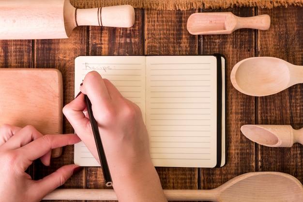 Frauenhand schreiben ein rezept in kochbuch