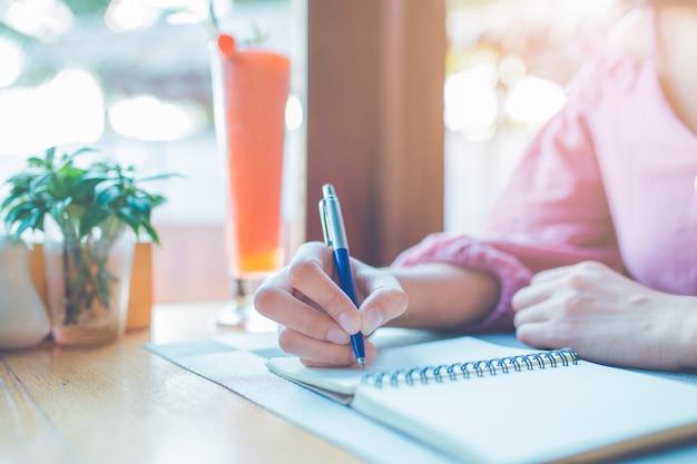 Frauenhand schreibt auf ein notizbuch mit einem stift.