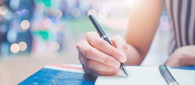 Frauenhand schreibt auf einen leeren notizblock mit einem stift auf einem hölzernen schreibtisch.