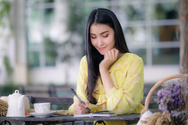 Frauenhand schreibt auf notizblock mit einem stift im garten