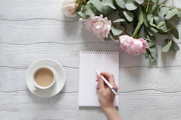 Frauenhand schreibt in ein notizbuch. tisch mit pfingstrosen und einer tasse kaffee draufsicht.