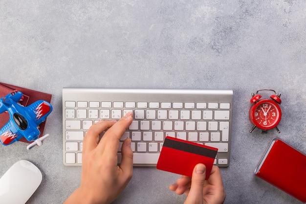 Frauenhand schreibt tastatur und nimmt kreditkarte nahe kleiner flugzeuguhr und -pässen