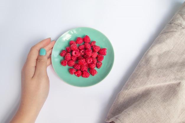 Frauenhand setzt eine grüne platte mit roten himbeeren auf eine weiße tabelle. frühstück und diät.