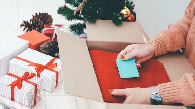 Frauenhand setzte die chrismas karte in weihnachtsgeschenkbox ein.