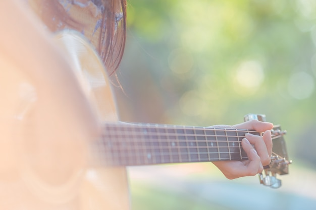 Frauenhand spielt akustisches guitarr im garten.