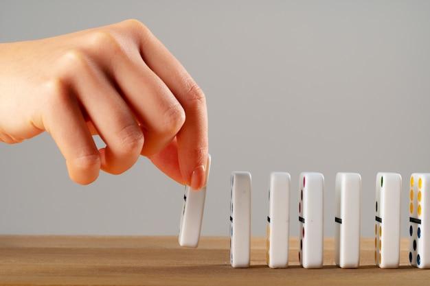 Frauenhand stürzt dominosteine. kettenreaktionsgeschäftskonzept
