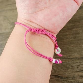 Frauenhand tragen rosafarbenes schnurarmband