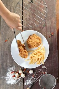 Frauenhand und gebratenes hühnerflügel mit pommes-frites auf hölzerner tabelle.