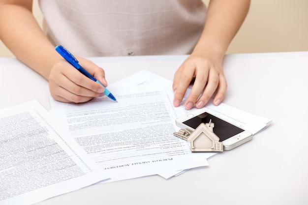 Frauenhand und hauptschlüssel. unterschriebener vertrag und schlüssel der immobilie mit dokumenten. konzept für echte e