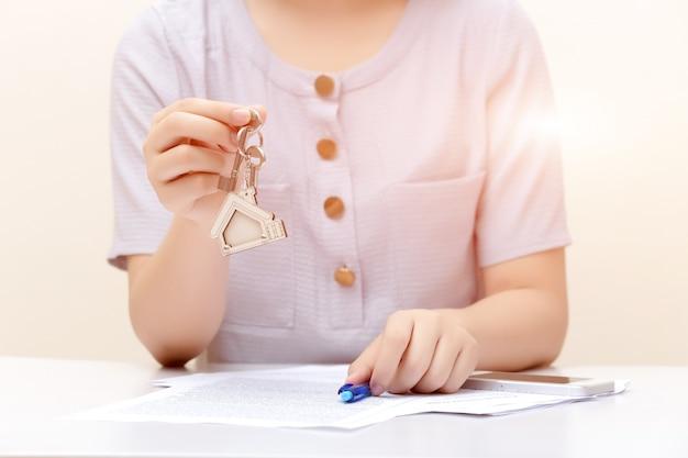 Frauenhand und hausschlüssel, unterzeichneter vertrag und schlüssel des eigentums mit dokumenten.