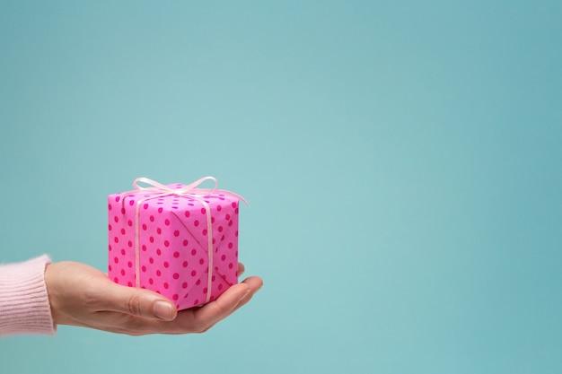 Frauenhand und rosa geschenkbox auf blauem kopierraumhintergrund. alles gute zum geburtstag.
