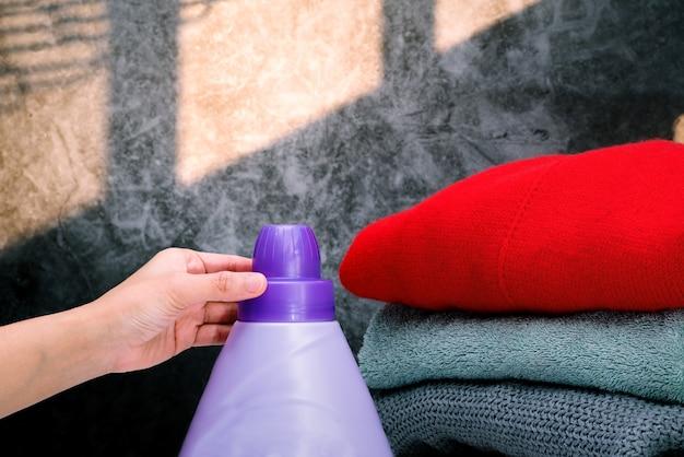 Frauenhand unter verwendung der waschmittelflüssigkeit, um stoff zu waschen