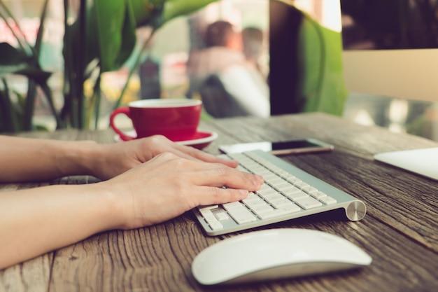 Frauenhand unter verwendung des laptops, der informationen an der kaffeestube sucht
