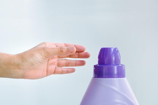 Frauenhand unter verwendung des reinigenden waschenden stoffes des flüssigen wäscheweichmachers