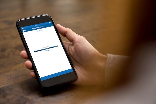 Frauenhand unter verwendung des smartphone, der online geld über internetbanking-anwendung überträgt