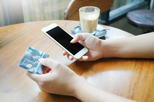 Frauenhand unter verwendung des smartphone für bewegliche verhandlung oder online kaufen