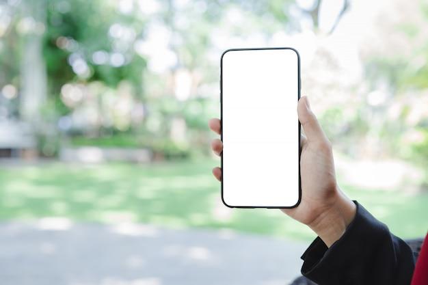 Frauenhand unter verwendung des smartphonemodells und des unscharfen grünen gartens