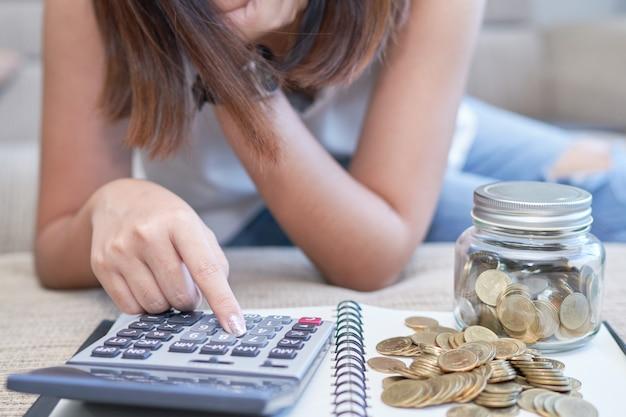 Frauenhand unter verwendung des taschenrechners mit goldmünzen und glasflasche