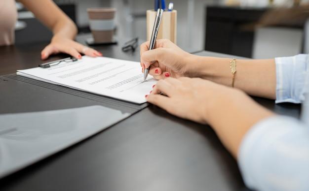 Frauenhand unterschreibt arbeitsvertrag