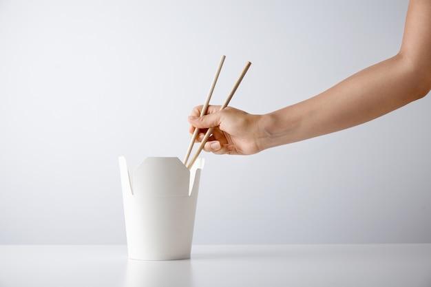 Frauenhand verwendet essstäbchen, um leckere nudeln von der leeren schachtel zum mitnehmen aufzunehmen, die auf weißer einzelhandelssetpräsentation isoliert wird