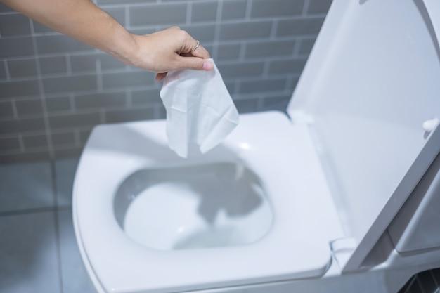 Frauenhand werfen papiertücher in die toilettenschüssel. konzept für reinigung, lebensstil und persönliche hygiene