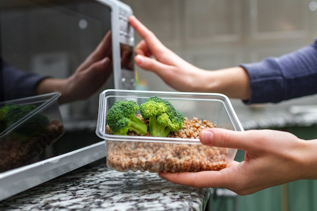 Frauenhand wird einen plastikbehälter mit brokkoli und buchweizen in der mikrowelle erhitzen