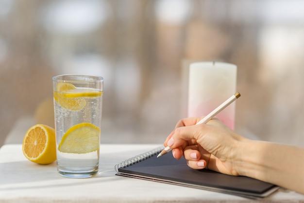 Frauenhand zeichnet in designerschwarznotizbuch