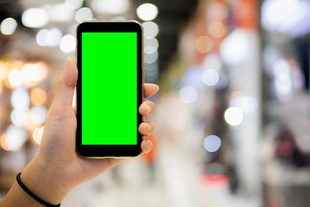 Frauenhand zeigt mobilen smartphone mit grünem bildschirm in vertikaler position